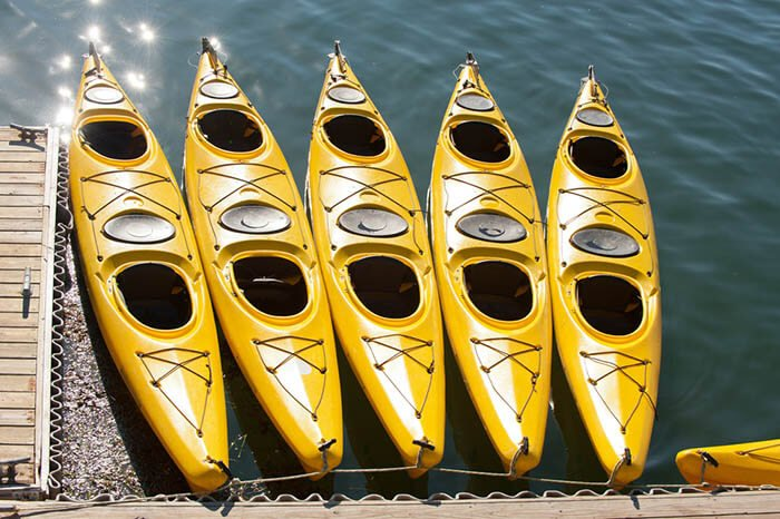 A row of yellow kayaks along the dock on a sunny day from your Maine realtor