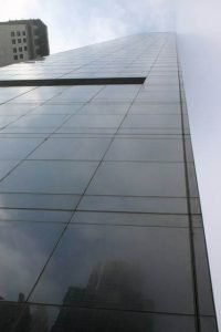Looking directly up at a glass skyscraper