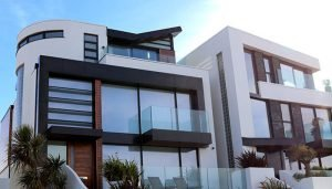 The exterior of a large, modern home with the sky reflected in the windows