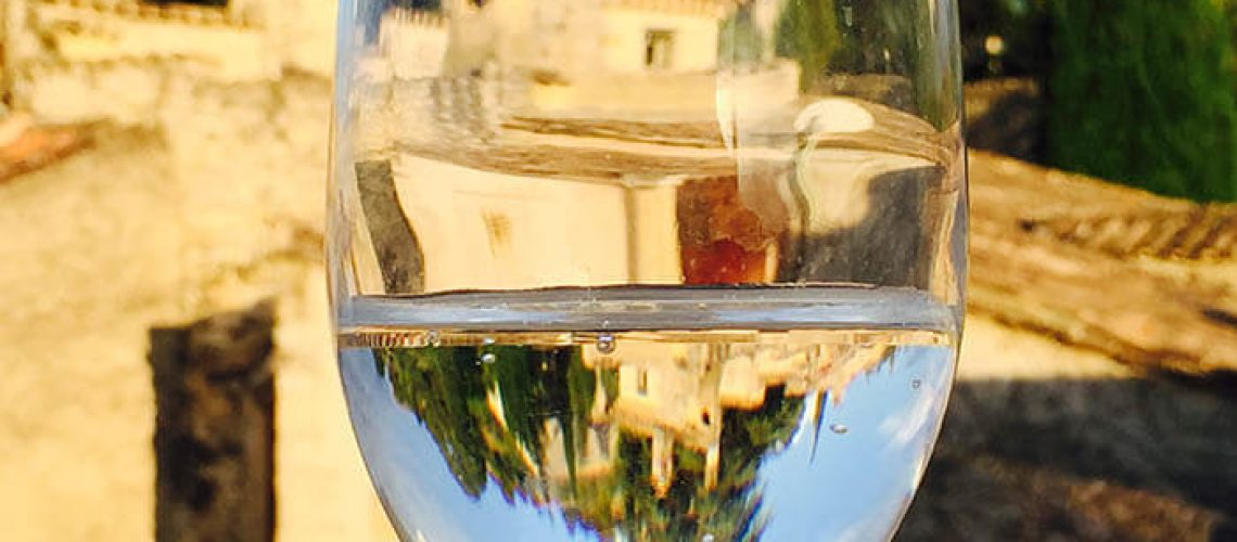 A glass of water with a reflection of a home